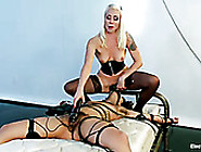 Blonde Mistress Wearing Corset Sits On Slave&...