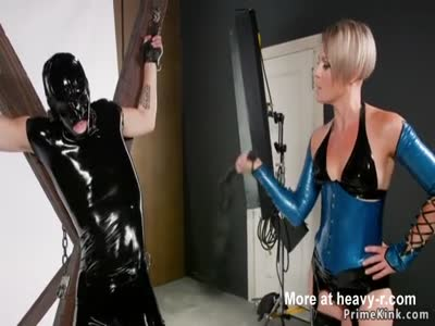 Domme Whips Male Slave In Latex Suit