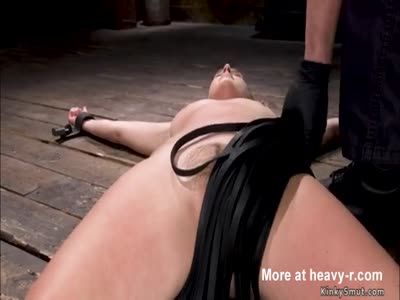 Shackled brunette slave is whipped