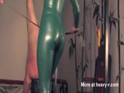Mistress in green latex whips slave upside down