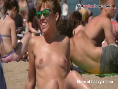 A nice babe goes topless on the beach