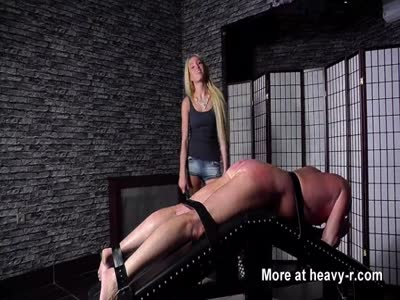Blonde hot dominatrix punishes her slave with leather strap